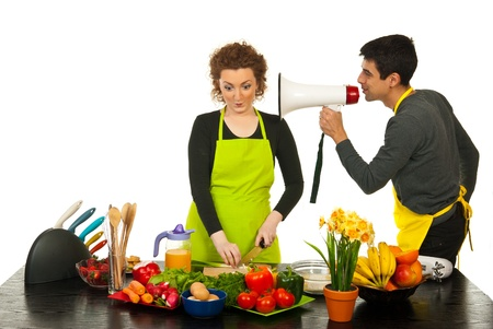 faster: Husband telling by megapone to his wife to cook faster against white background Stock Photo
