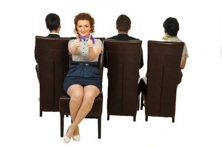 Successful woman sitting on chair out of the crowd and giving thumbs Stock Photo
