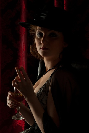 Retro woman with hat in darkness smoking and drinking wine photo
