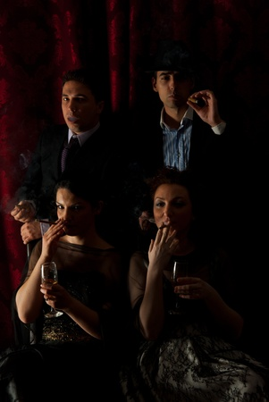 cigars: Retro two couples smoking in darkness and drinking wine