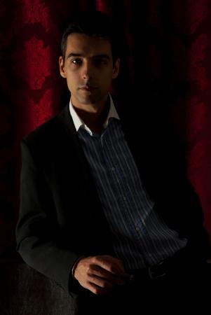 Elegant business  man in darkness in club holding cigar