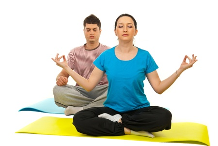 Couple doing yoga and sitting on gymnastics mats isolated on white background photo