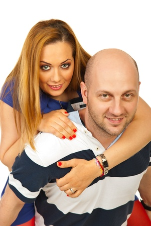 Happy bald man giving piggy back ride to his wife isolated on white background photo