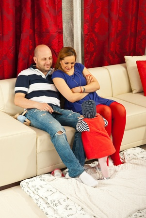 Cheerful mother and father talking with their baby in living room photo