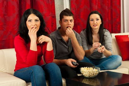 Three people sitting on couch watching tv at sad movie and eating popcorns photo