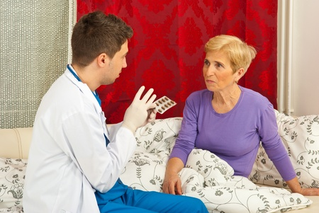 Doctor man explain to senior sick woman how to take the medicines and sitting on couch in home photo