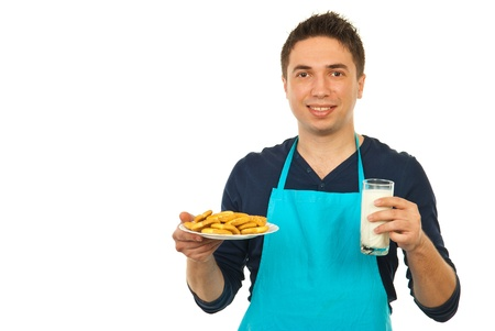Happy man with blue apron holding glass with milk and biscuits on plate isolated on white background photo