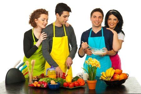 Cheerful four friends preparing dinner together in kitchen against white background photo