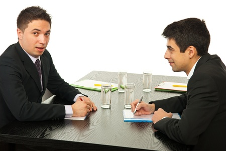 Two young business men talking at meeting together and sitting on chairs at table photo