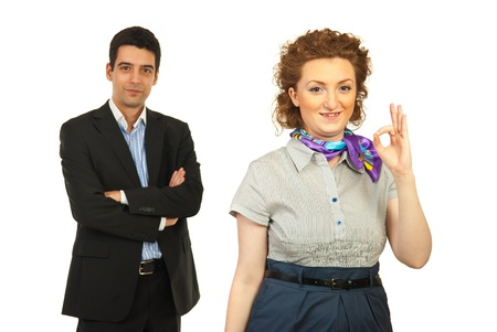 Successful team of two business woman with woman in front of camera showing okay sign hand gesture isolated on white background photo