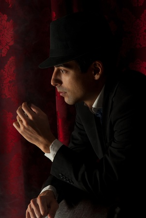 Elegant man with hat smoking in the night  photo
