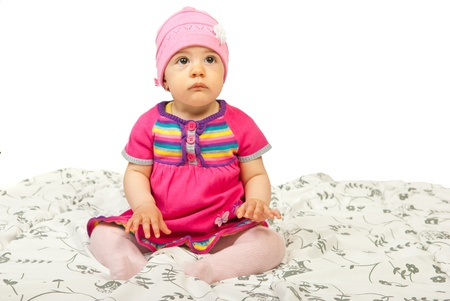 hait: Baby girl in  pink dress sitting in bed and looking up isolated on white background