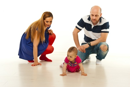 Parents looking at their baby girl crawling isolated on white background photo