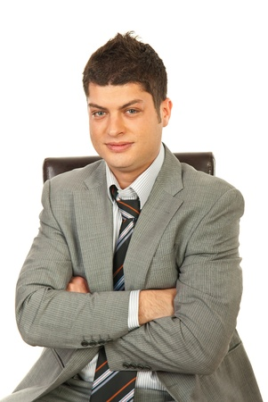 Young manager man sitting on chair with arms folded isolated on white background photo