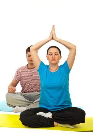 Young couple doing yoga and sitting on gymnastics mats against white background photo