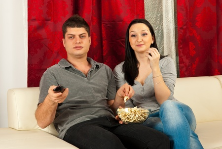 Couple watching movie at tv and eating popcorn photo
