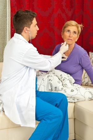 Doctor man examine senior woman heart beats home photo