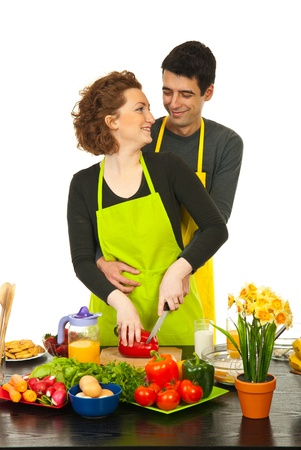 Loving couple laughing and standing in embrace while wife cutting pepper against white background photo