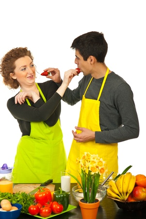 Couple having fun with strawberries in their kitchen photo