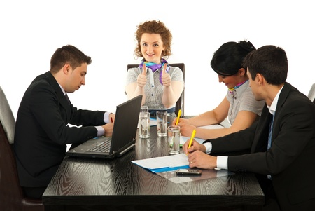 Business woman giving thumbs up at meeting while her colleagues working photo