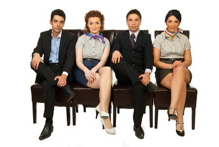 Row of four business people team standing on chairs with legs crossed and waiting isolated on white background photo