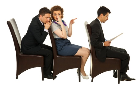 Businesswoman telling secret about first colleague man on chair to business an who listening her with closed eyes  and sitting all in a row on chairs Foto de archivo
