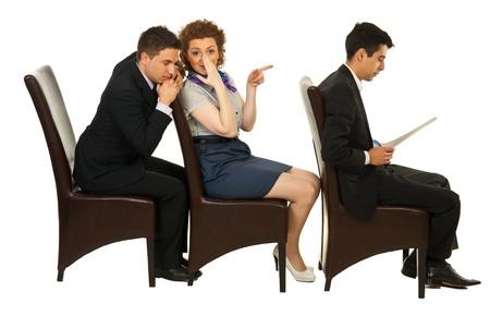 Zakenvrouw vertellen geheim over de eerste collega man op de stoel om zaken een die haar te luisteren met gesloten ogen en zitten allemaal in een rij op stoelen Stockfoto