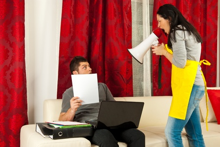 Housewife shouting by megaphone to her husband who working to much from home photo