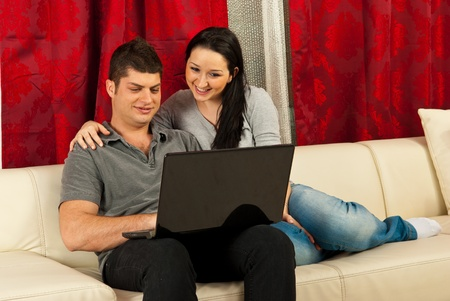 Happy couple using laptop and sitting on couch home photo