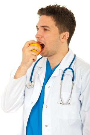 Doctor man looking away and eating an apple isolated on white background photo