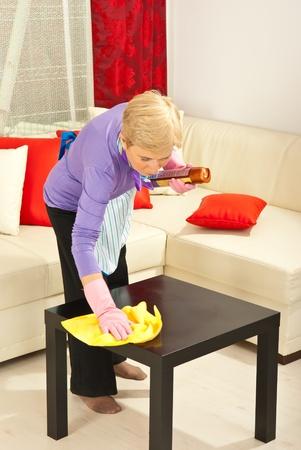 Vrouw veeg stof met een doek op de tafel in huis