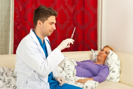 Doctor prepare syringe with treatment for sick senior woman home Stock Photo - 13135752