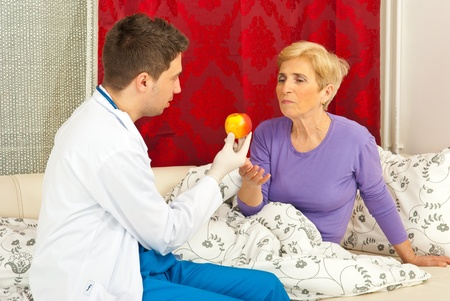 Doctor giving apple to senior woman home photo