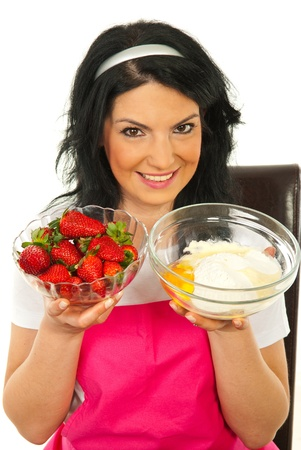 Woman showing bowls with strawberries and flour egg ,ingredients for preparing cake photo