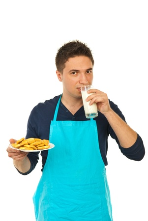 Man in kitchen wearing blue apron drinking milk and holding biscuits on plate isolated on white background photo