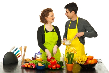 Happy couple cooking together and having conversation against white background photo