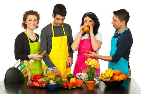 Vrolijke vier vrienden met kleurrijke schorten samen koken in de keuken Stockfoto