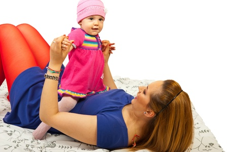 Lying mother playing with her baby girl over white background photo