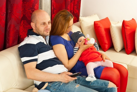 Father looking at tv and mother feeding baby and sitting together on couch in their living room photo