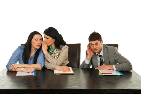 Business woman telling secret to her colleague and other colleague man trying to hear them in office
