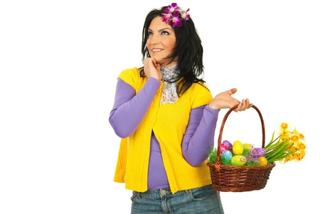 Happy Easter woman dreaming with open eyes and holding basket with flowers and eggs photo