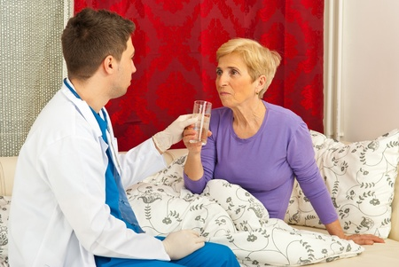 Nurse man giving glass of water to senior woman in bed home and having conversation Stock Photo - 13202932