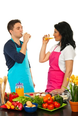 Couple drinkign fresh products in their kitchen and taking a break from cooking photo