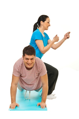 Man doing hard push ups with girlfriend on his  back who holding chronometer and counting  Stock Photo - 13240640