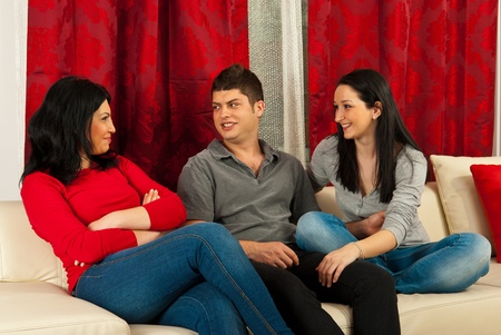 Three happy friends having conversation home and sitting together on sofa photo