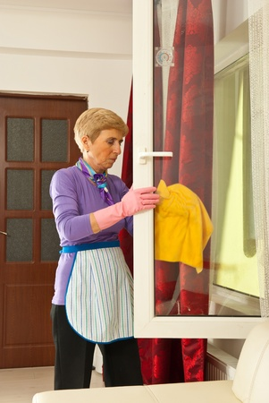 Senior woman cleaning big window home and being serios photo
