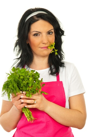 Beauty woman eating parsley and holding fresh bouquet of parsley and dill  isolated on white abckground photo