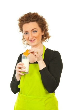Woman put biscuit in milk isolated on white background photo