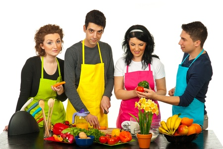 four people: Happy friends with colorful aprons cooking together against white background