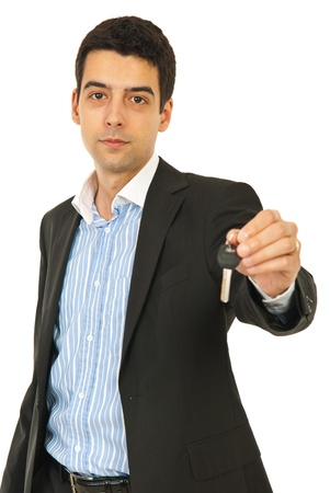 car keys: Young business man giving house key isolated on white background